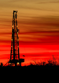 natural gas drill rig at sunset