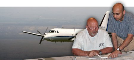 Bob Hannigan (seated), Director of Flight Operations and Chief Pilot, reviews flight plans with scientist Rahul Zaveri to plan for a research campaign.