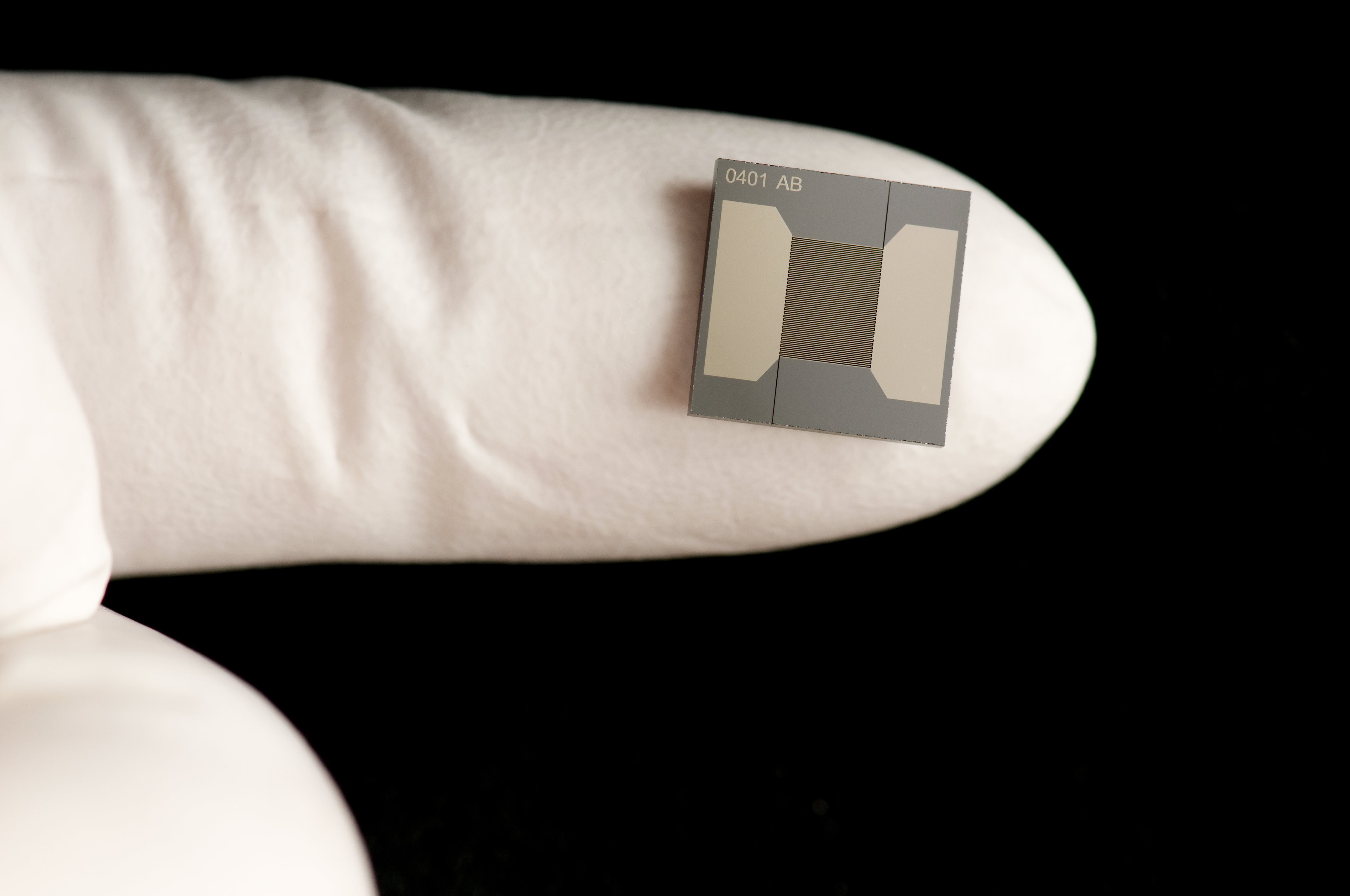 IMS Microchip shown on gloved finger