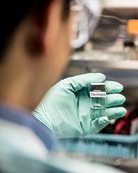 Scientist holding vial labeled electrolytes