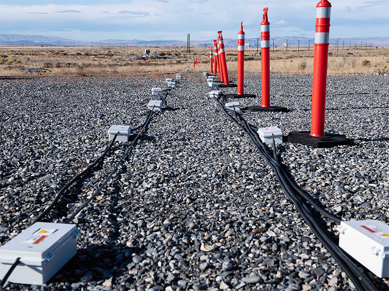 Two lines of cables, small gray metal boxes, and orange cones go off into the Hanford desert.