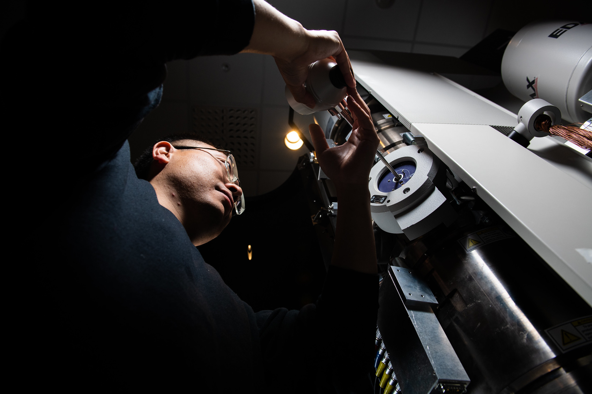 Researcher Yang He adds a sample to the environmental transmission electron microscope