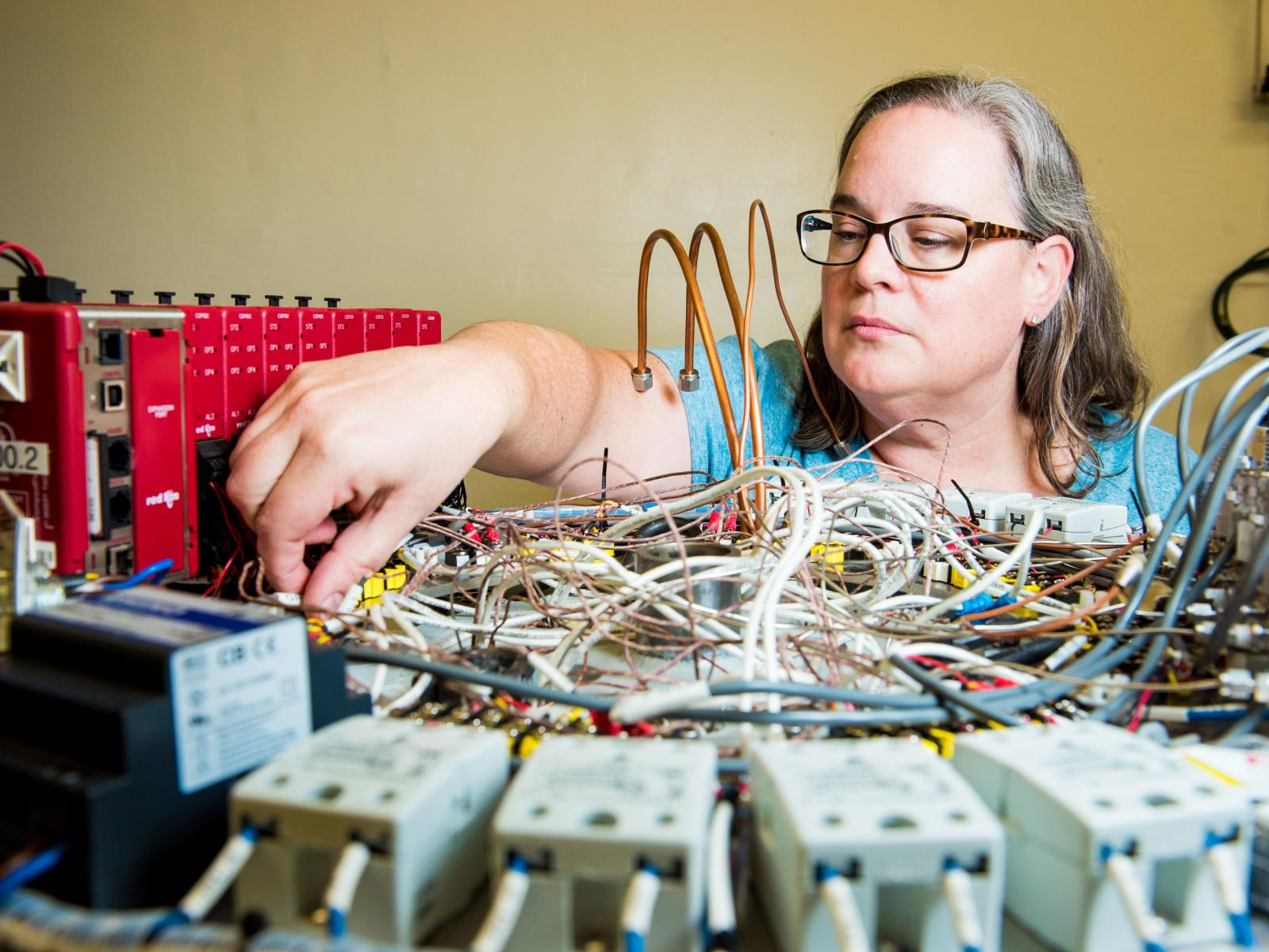 Researcher Heather Colburn reaches across a neck-high platform to connect wires on scientific equipment.
