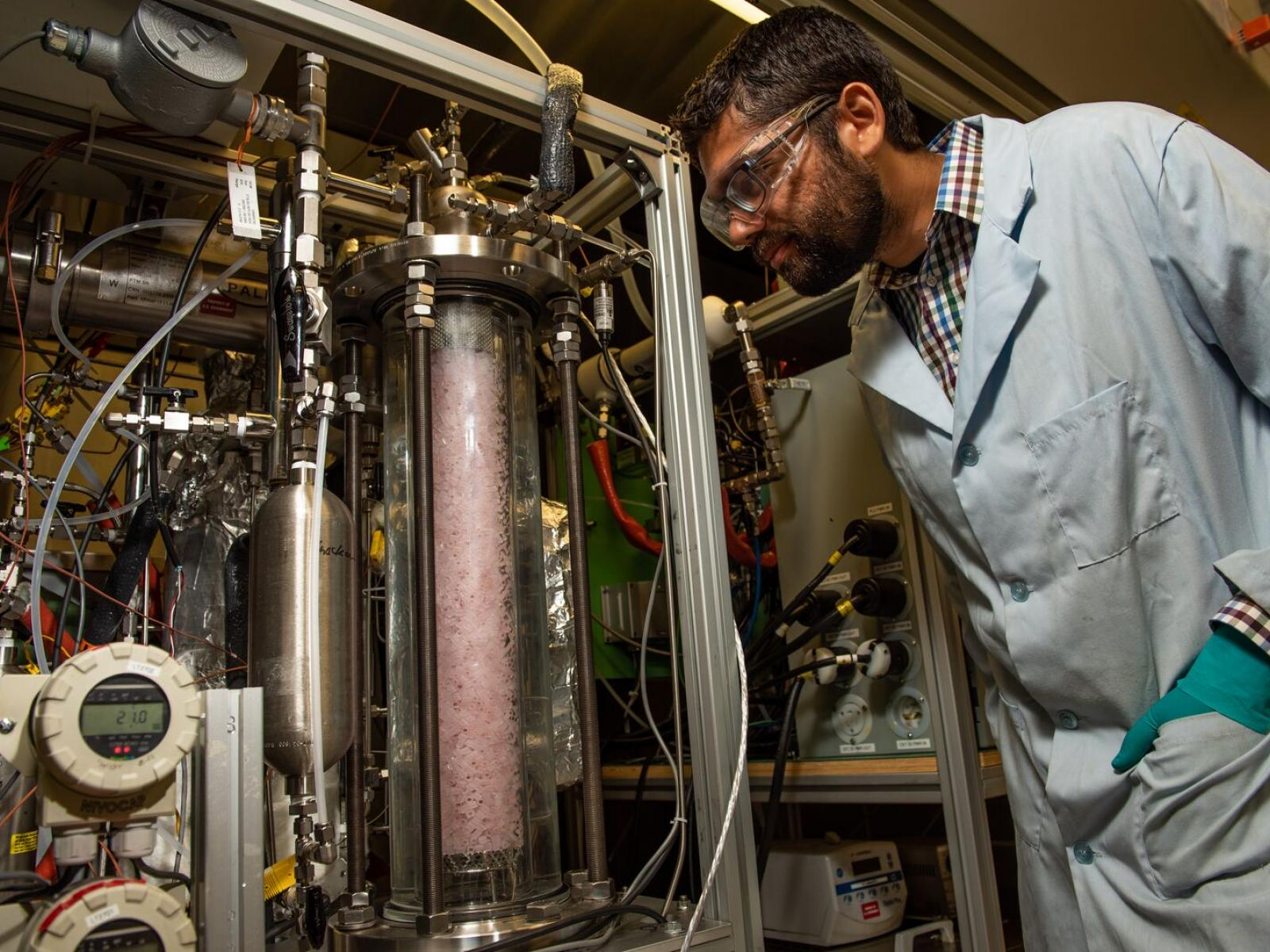Chemical engineer Dushyant Barpaga observes the Laboratory Continuous Flow System, which researchers use to analyze the performance of CO2 capture solvents, like EEMPA, at small scales before testing at greater capacities.