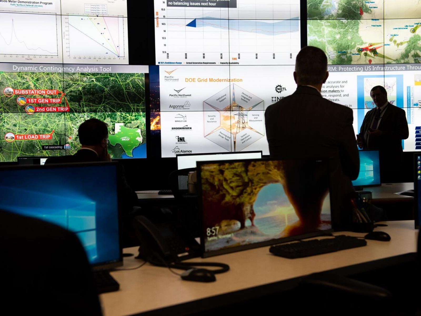 Researchers discuss the power grid in an electrical control room