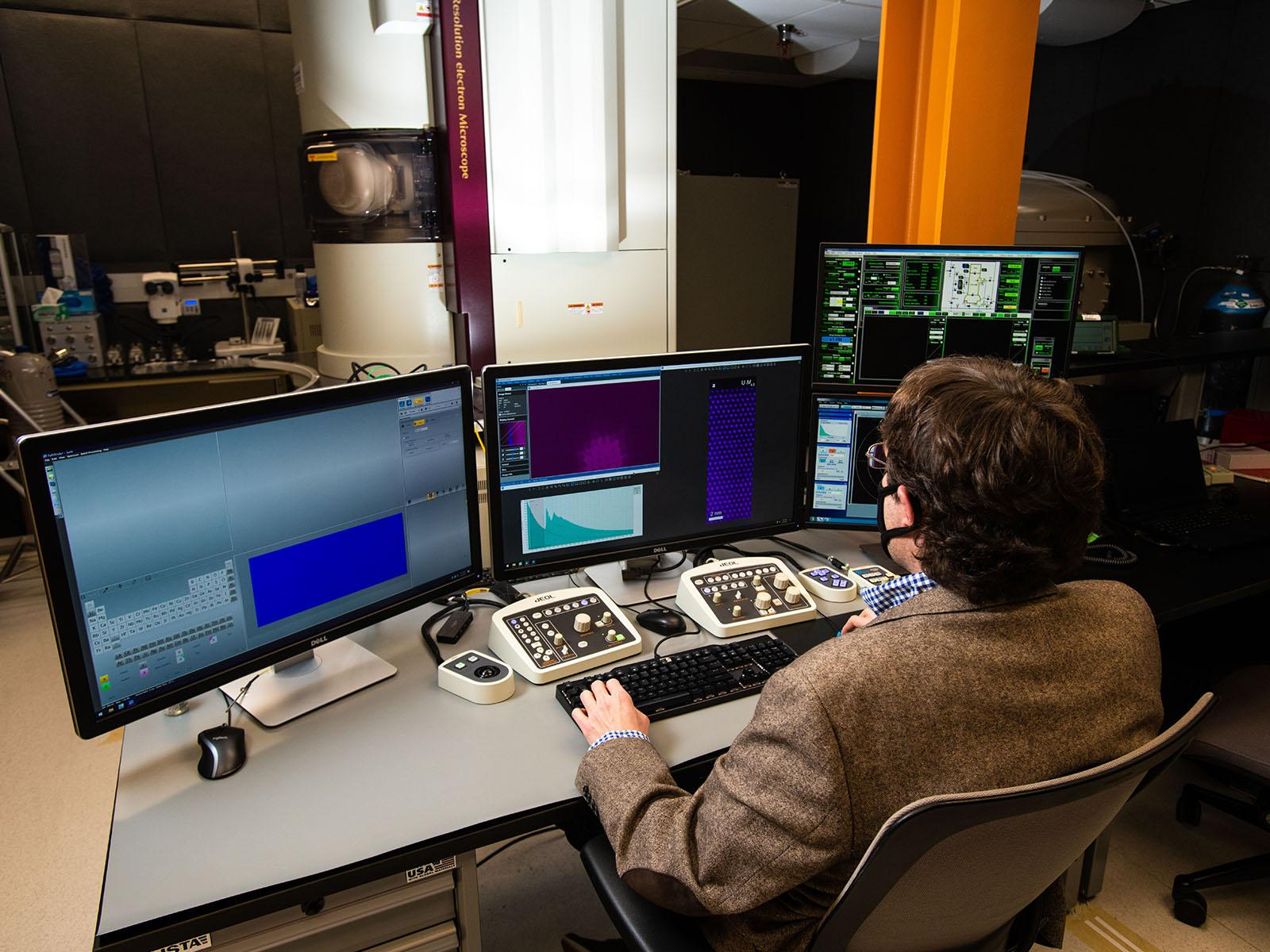 Scientist Steven Spurgeon sits at a desk with a keyboard and multiple monitors while he controls a huge microscope in the room.