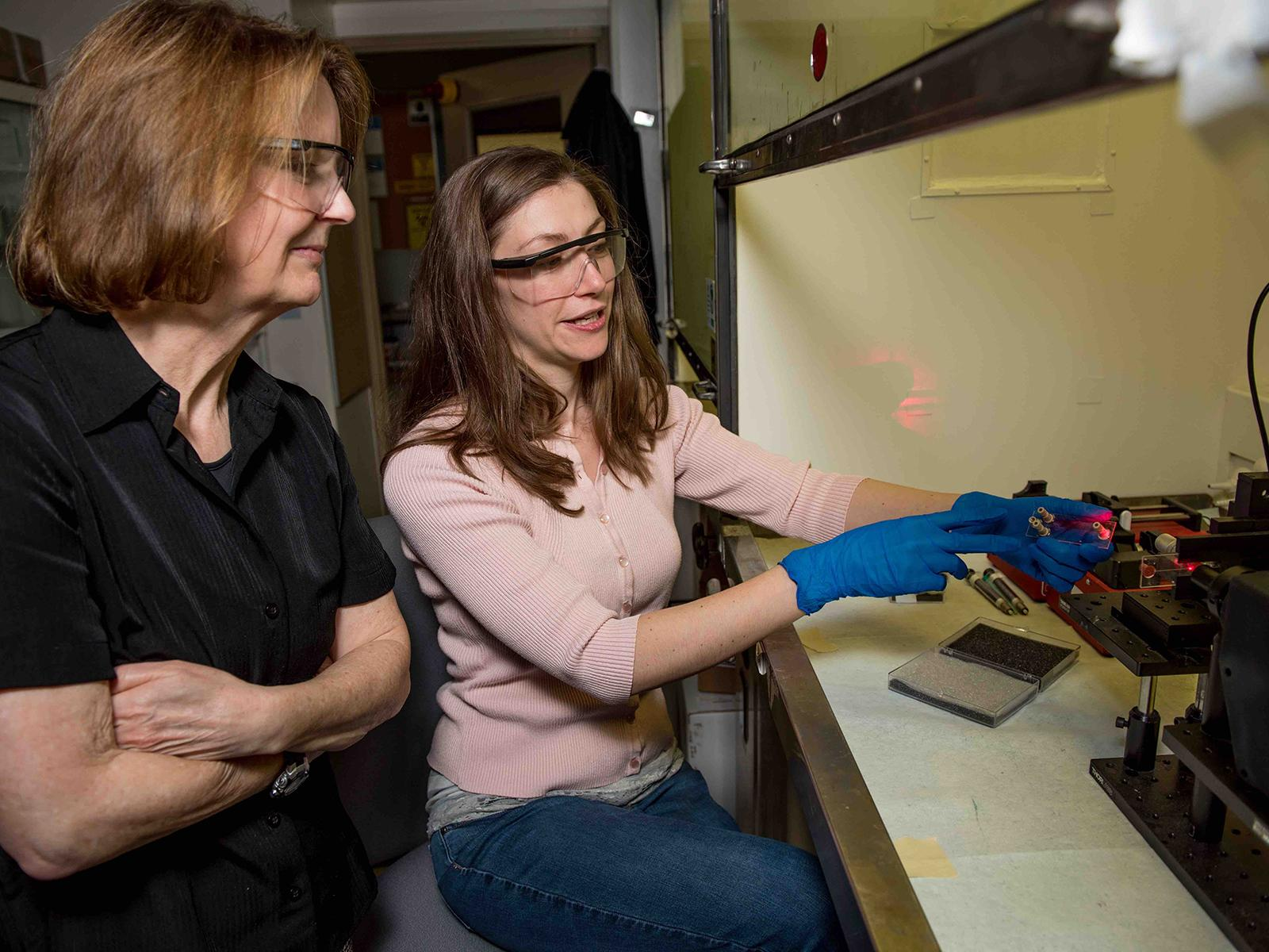 Scientists Sue Clark and Amanda Lines use a laser for nuclear chemistry research.