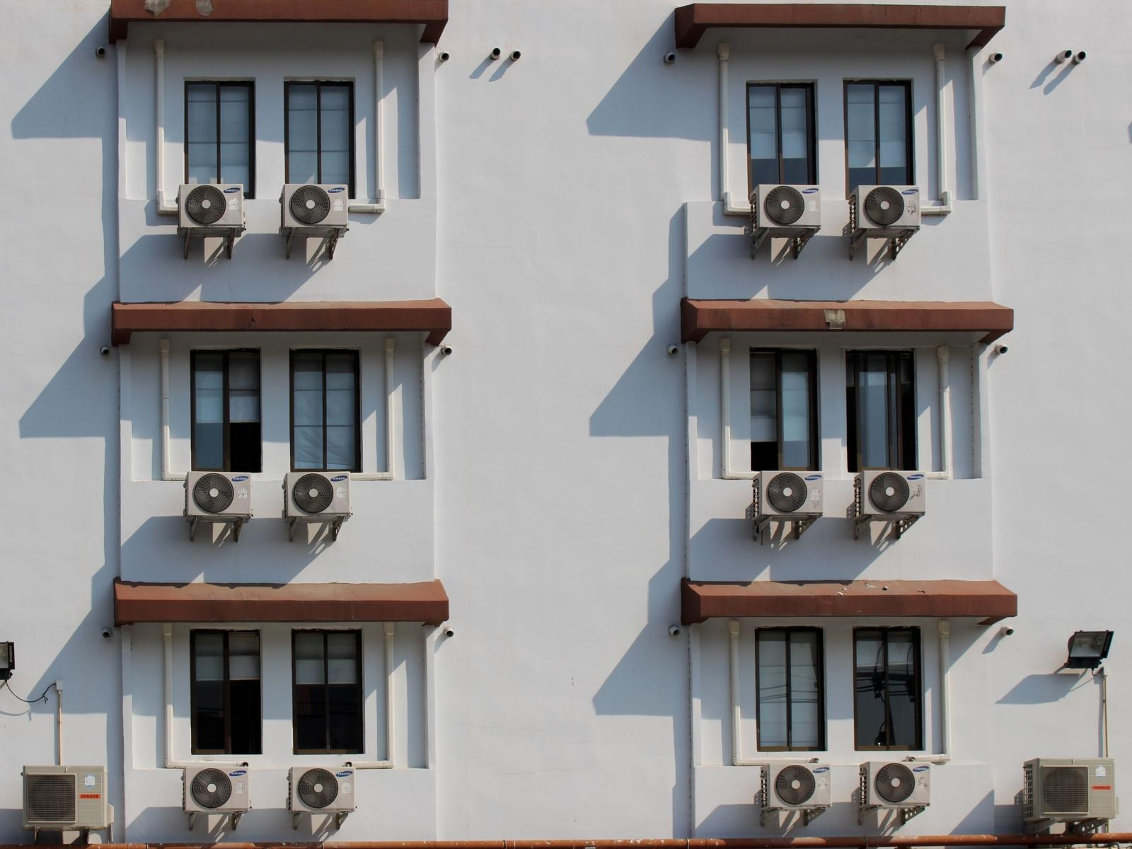Air conditioning units sit outside a hotel building face, one attached to each window.