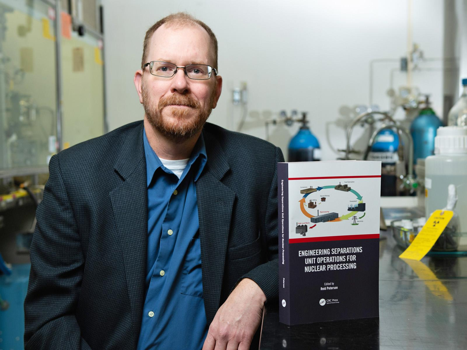 Scientist Reid Peterson shows a book about nuclear chemistry while sitting in a research lab.