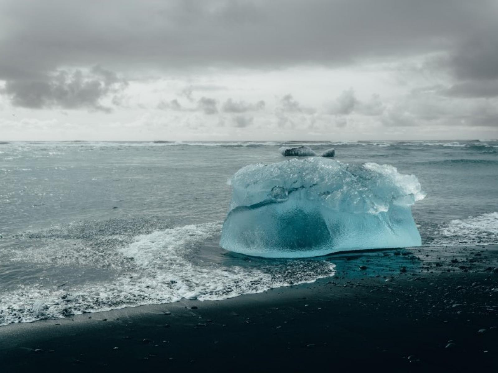 a blue-green iceberg on a dark beach