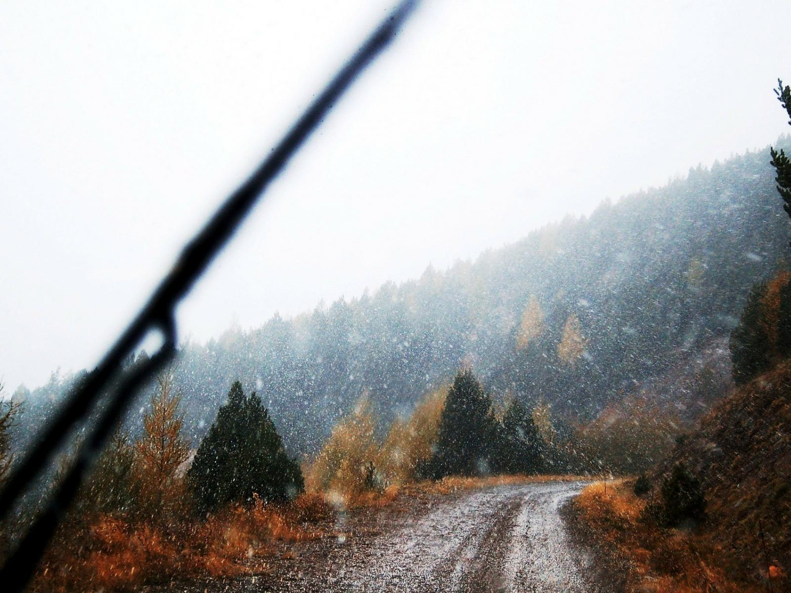 view through a car windshield of a rainy drive on a dirt mountain road