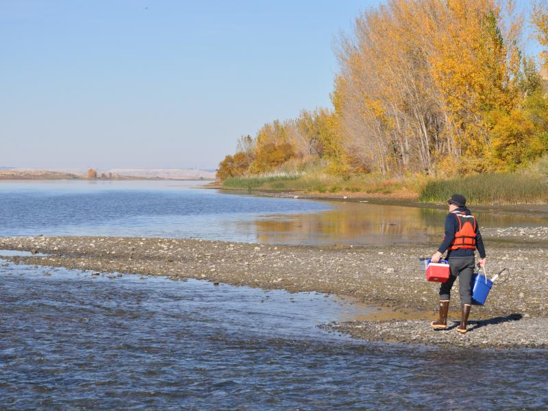 person wearing a life jacket and rubber boots walking along a rocky riverbank carrying a cooler