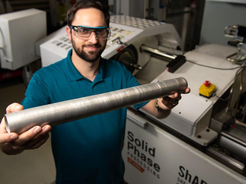 Researcher hold tube extruded by the ShAPE machine