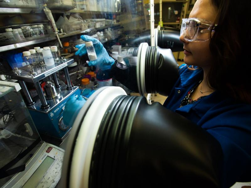 Woman working at lab glove box.