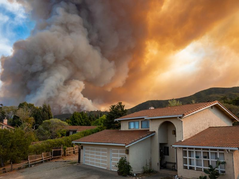 Wildfire, ignited by dry lightning, rages just behind a California home. (© David A. Litman | Shutterstock.com)