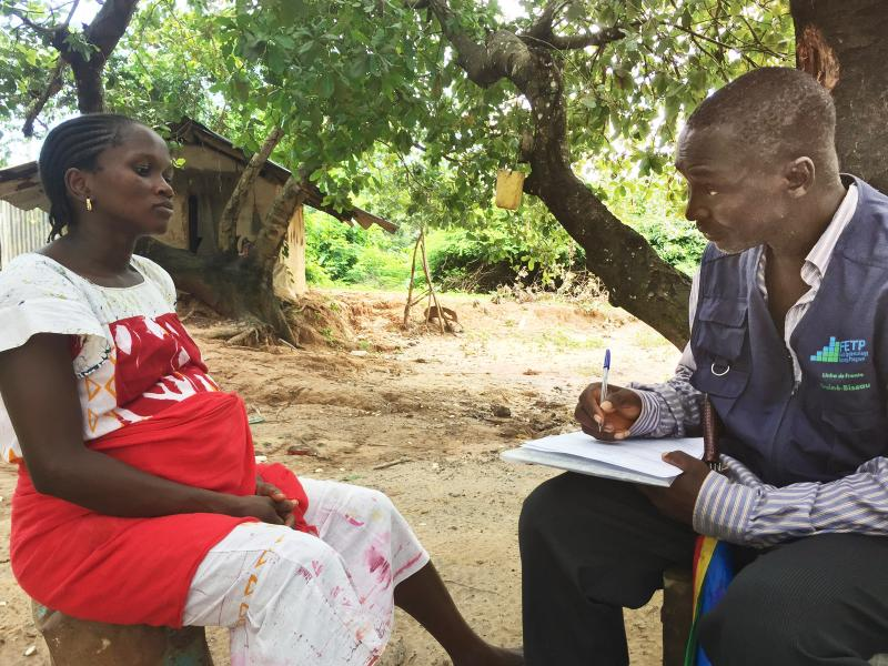 a man interviewing a pregnant woman during an infectious disease screening