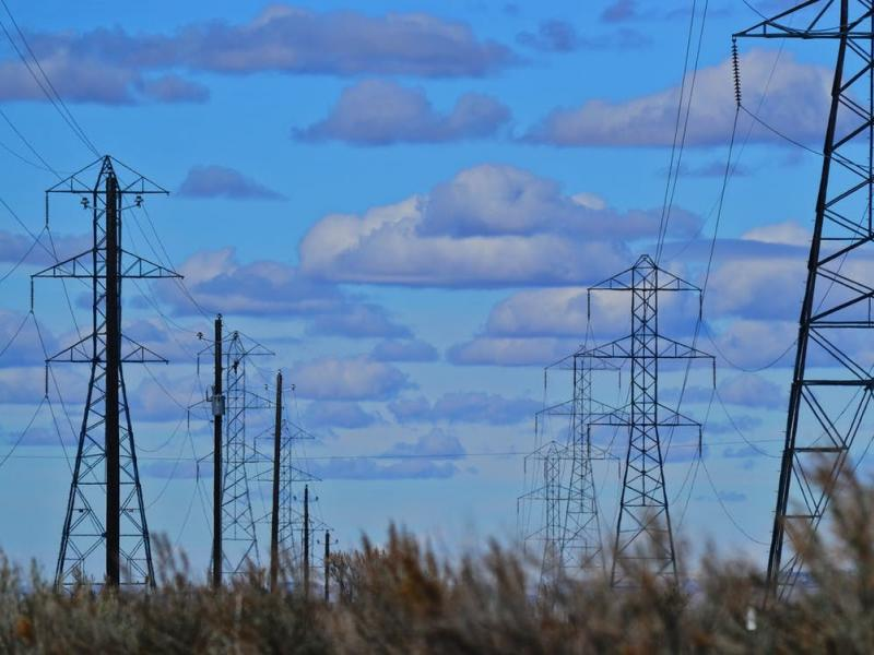 Power lines and poles in the foreground of a cloudy blue sky