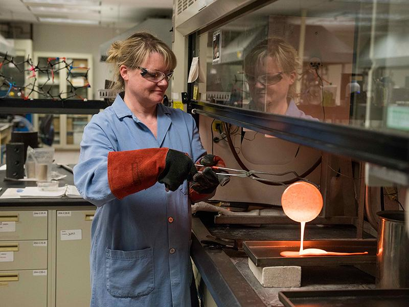 A female researcher wearing a blue lab coat and heat-resistant safety gloves pours molten glass out of a metal crucible onto a metal tray.